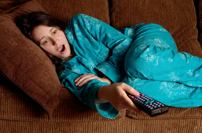 Photo of a Woman yawning while changing channels