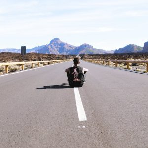 A young person sits in the middle of a highway