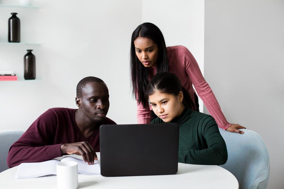 3 people crowd around a laptop